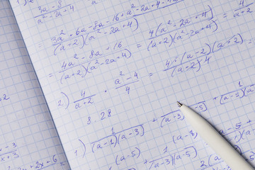 Algebraic calculations in open graph notebook with white pen. White paper with math fractions, top view