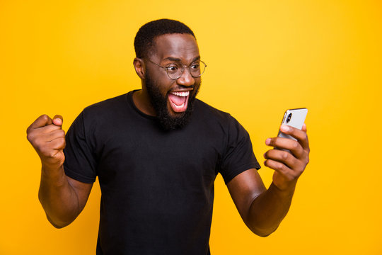 Photo of overjoyed crazy casual brown haired bearded man in eye glasses t-shirt rejoicing in victorious event expressing emotions on face isolated vivid color yellow background