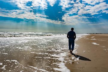 man walking on the beach under rays of sun