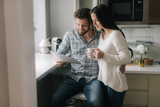 Attractive young married couple studying mortgage documents together. Beautiful girl holding a cup of coffee in her hands. Daily life of a male and female in apartment.