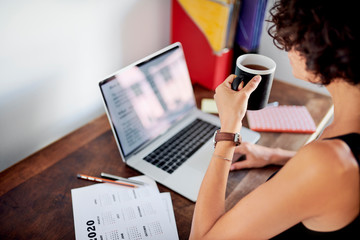 Woman working on laptop and drinking tea.