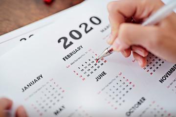 Person underlines Valentine's day in calendar.