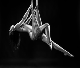 Beautiful brunette girl gymnast wearing lingerie sensually and feminine hanging, posing on canvas. Advertising, commercial and artistic monochrome noir design. Black background.
