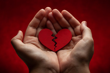 Woman holds broken heart in her hands. Crack in the red heart, Breaking the relationship