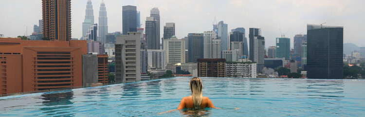 In de dag Kuala Lumpur Young happy girl swimming alone in the infinity pool on rooftop in Kuala Lumpur in Malaysia. Horizontal photo.