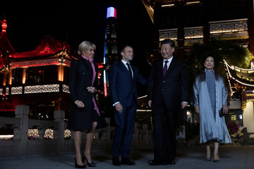 Chinese President Xi Jinping and Chinese first lady Peng Liyuan stand with French President Emmanuel Macron and French first lady Brigitte Macron for a group photo after having dinner at the Yu Garden district in Shanghai