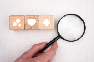 Doctor hand arranging wood block stacking with healthcare and medical icon, insurance for your health and search.