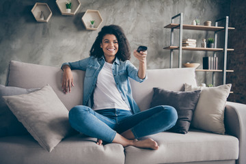 Photo of pretty dark skin wavy lady homey mood holding tv remote control changing channel searching favorite humor show sitting comfy couch casual denim outfit flat indoors