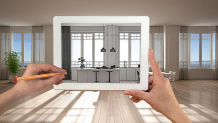Hands holding and drawing on tablet showing modern white kitchen with panoramic windows CAD sketch. Real finished interior in the background, architecture design presentation