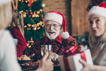 Phot of grandfather positive cheerful smiling in eye glasses spectacles wearing santa hat headwear...