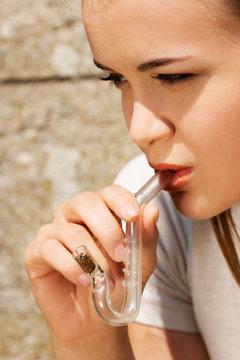 Young woman smoking cannabis weed or hashish of pipe. Medical marihuana.