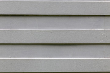 White Wood Lath. straight striped whiteboard. House wall outside. Gray wood wall.
