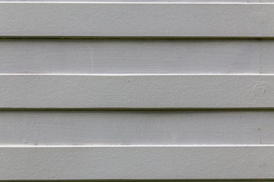 White Wood Lath. straight striped whiteboard. House wall outside. Gray wood wall.