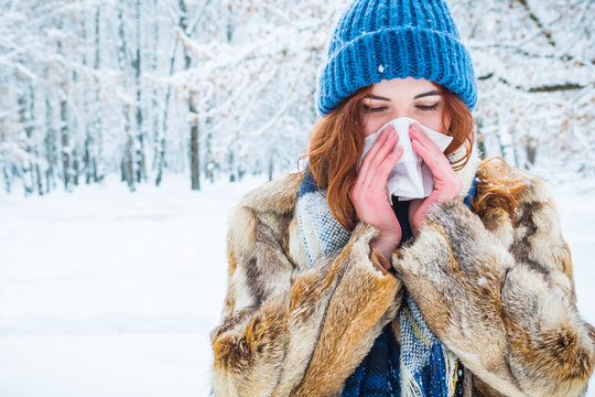 portrait of a young woman in the winter forest. a beautiful girl sneezes into a napkin. get sick in winter.