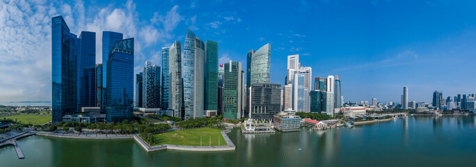 High rise office towers of the Singapore central business and financial district aerial panorama on a sunny morning including waterfront and reflection