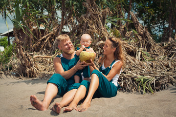 Happy hipster family funny picnic on beach - mother, father feed baby boy. Little son eat fruits with fun, drink fresh coconut. Healthy lifestyle, active people walking on summer vacation with child.