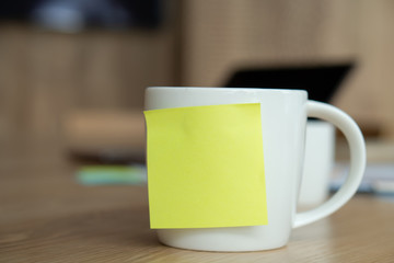 A white coffee cup with a blank yellow post-it on the cup. Resting on the desk and laptop is placed on the back.