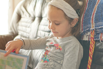 Blonde little girl with cochlear implant reading a book at home. Hear impairment and deaf community...