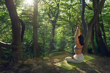 Yoga outdoor. Woman doing yoga exercises meditation in nature. Concept of healthy lifestyle relaxation. Woman practicing yoga on the park. Body relaxation. Asana yoga pose. Harmony with nature.