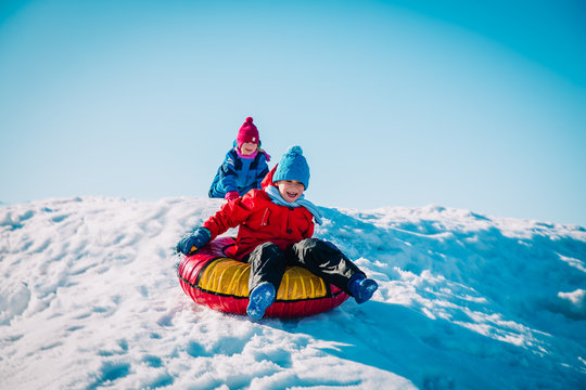 happy cute boy and girl slide in winter snow