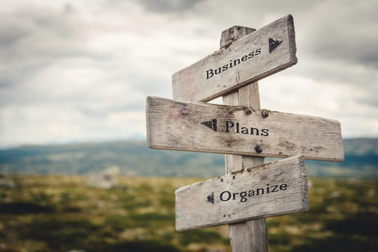 Business, plans and organize wooden signpost outdoors in nature. Quote, message, road, business, success concept.