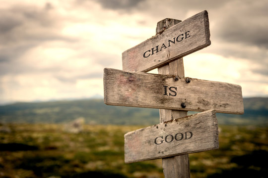 Change is good quote on wooden signpost in nature with moody background. Motivational, move on, changes, choice, choices concept.