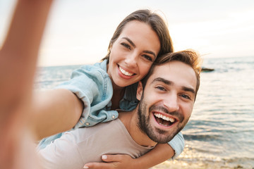 Image of man giving piggyback ride woman and taking selfie photo