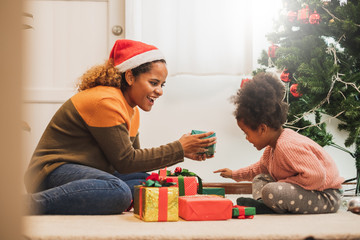 Young black african mother giving Christmas present gift box to her daughter, merry christmas and...