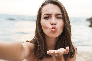 Image of nice woman sending air kiss and taking selfie photo