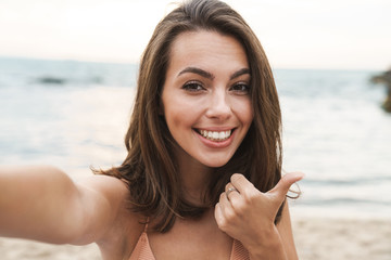 Image of smiling caucasian woman showing thumb up and taking selfie