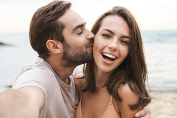 Image of young happy man kissing and hugging woman while taking selfie
