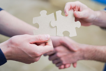Cooperation puzzle partnership and handshake teamwork in business group company.