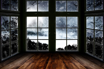 Wall Mural - Table top board with big window background and beautiful snowy winter landscape outside. Moonlight winter night.