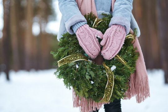 Christmas wreath in  beautiful woman hands in snow forest. The young girl is dressed in a blue coat, in a light knitted hat, scarf and mittens.seasonal holidays, adorning. Christmas, New year.