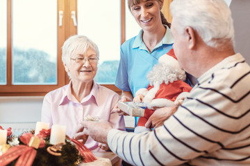 Seniors in nursing home exchanging presents for Christmas