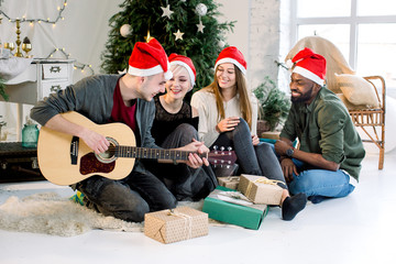 Picture showing group of four friends celebrating Christmas at home. Young Caucasian man is playing guitar and the girls and African man are smiling and singing carols