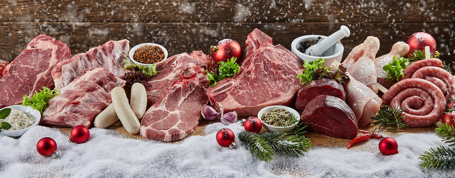 Christmas banner with assorted raw meat for a BBQ