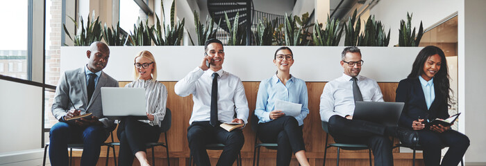 Diverse businesspeople smiling while waiting together in an offi