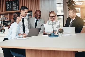 Smiling group of diverse businesspeople working around an office
