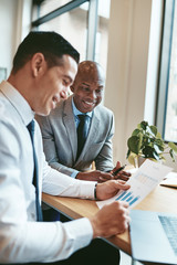Two diverse businessmen smiling while reading paperwork in an of