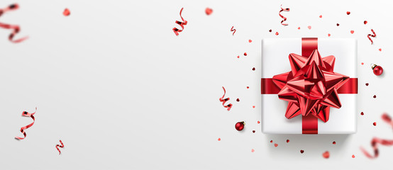 Fototapete - White gift box with red ribbon and bow, red decoration, sparkles, confetti on white background. Merry Christmas and Xmas card. Happy Birthday postcard, top view, realistic vector