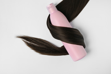 Wall Mural - Shampoo bottle wrapped in lock of hair isolated on white, top view. Natural cosmetic products