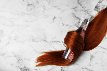 Spray bottle wrapped in lock of hair on white marble background, flat lay with space for text....