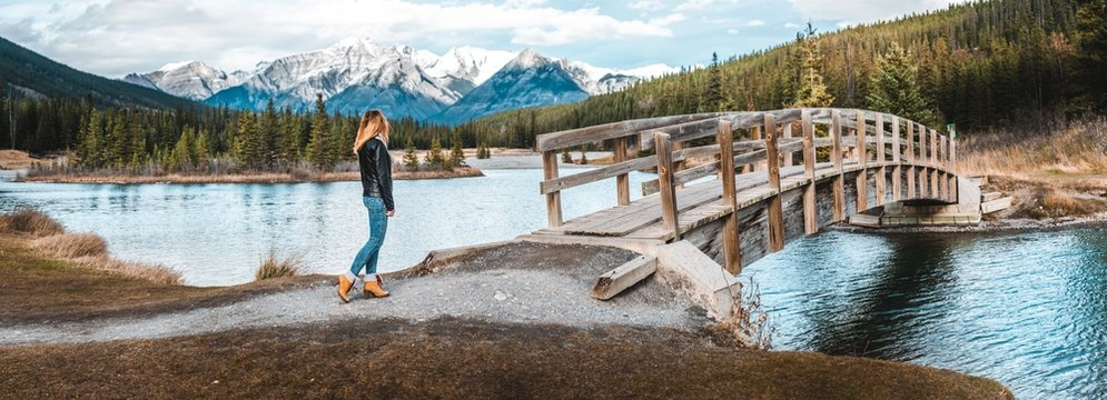 Girl in leather jacket about to cross bridge infront of mountains