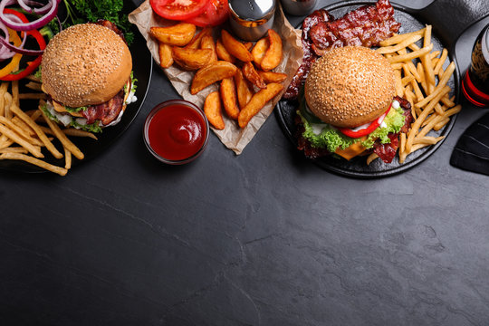 Flat lay composition with fresh bacon burgers and fries on grey table. Space for text