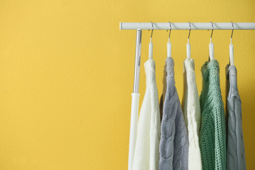 Collection of warm sweaters hanging on rack near yellow wall, closeup. Space for text