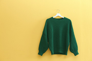 Hanger with stylish sweater on yellow wall