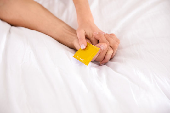 Woman and man holding condom together on bed, closeup. Safe sex concept