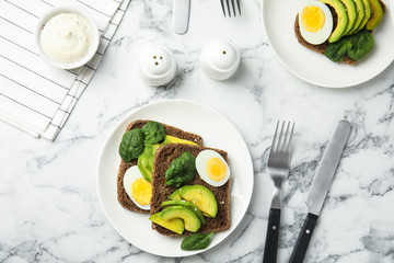 Flat lay composition with avocado toasts on white marble table