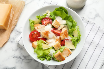 Delicious fresh Caesar salad in bowl on white marble table, flat lay